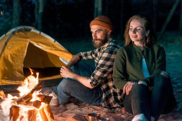 Acampar pareja sentados juntos por fogata