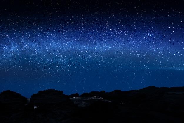 Acantilado rocoso con brillantes de las estrellas.