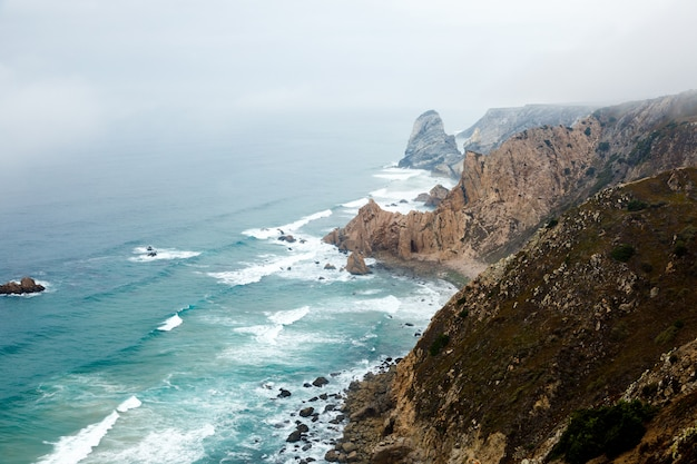 Los acantilados están cubiertos de niebla en el océano atlántico, un paisaje natural en cabo da roca, cerca de la ciudad de cascais, portugal. la capa más occidental del continente euroasiático.