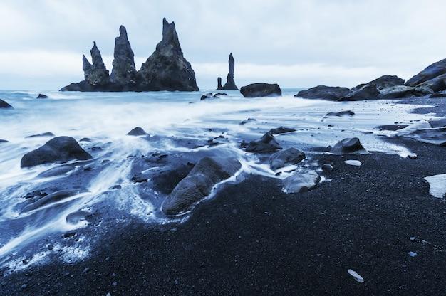 Acantilados de reynisdrangar. playa de arena negra en islandia.