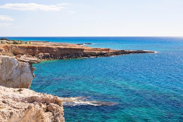 Los acantilados de la roca y el mar aúllan con agua azul cerca de protaras, isla de chipre.