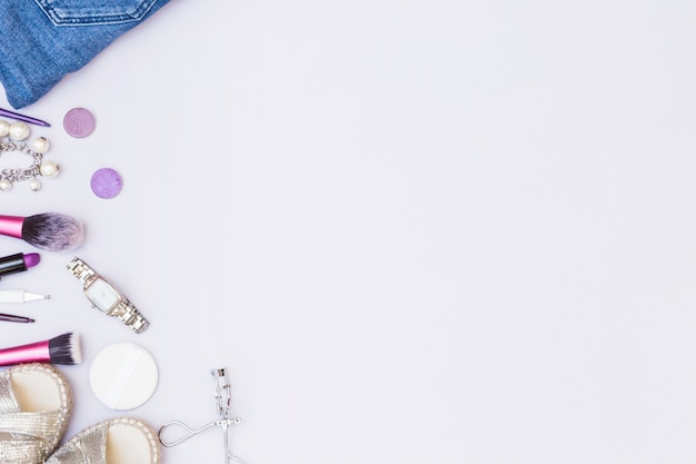 Accesorio femenino con productos cosméticos sobre fondo blanco