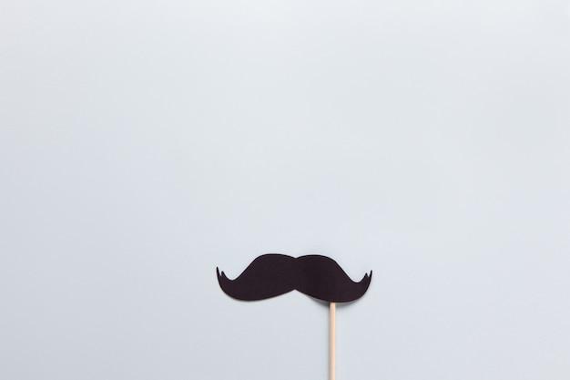 Accesorio en forma de bigote negro en palo sobre fondo gris