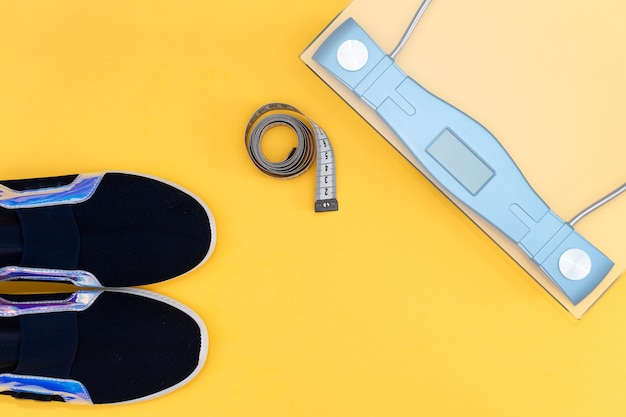 Accesorios de la aptitud en un fondo amarillo. zapatillas de deporte, botella de agua, auriculares y mancuernas.