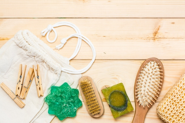 Accesorios de baño sin desperdicio, cepillo de sisal natural, peine de madera, jabón sólido, bolsa de lona y pinzas de madera sobre un fondo de madera natural