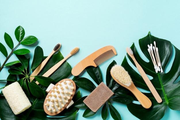 Accesorios de baño ecológicos o herramientas de spa en hojas monstera sobre fondo azul. fondo de hormigón cosmético. concepto de belleza y desperdicio cero.