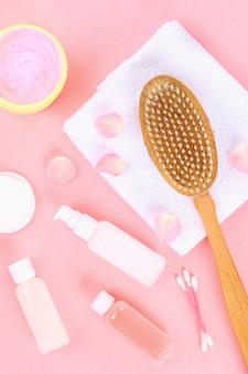 Accesorios de baño sobre un fondo rosa pastel.