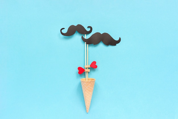 Los accesorios de bigote de papel de pareja en el palo sujetan el corazón de la pinza en el cono de galleta de helado sobre fondo azul