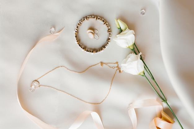 Accesorios de boda de la novia: brazalete, aretes, cadena con colgante y flores de eustoma sobre fondo beige