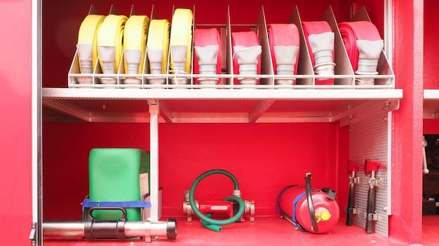 Accesorios para bomberos, extintor y manguera, herramientas y equipo en el camión de bomberos rojo.