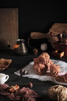 Accesorios de café y céfiros caseros en la mesa de madera de la cocina. malvaviscos hechos de manzanas y bayas frescas. postre saludable y delicioso con café para el desayuno.