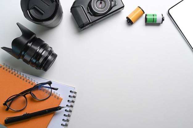 Accesorios de cámara, cuaderno y espacio de copia en el lugar de trabajo del fotógrafo.