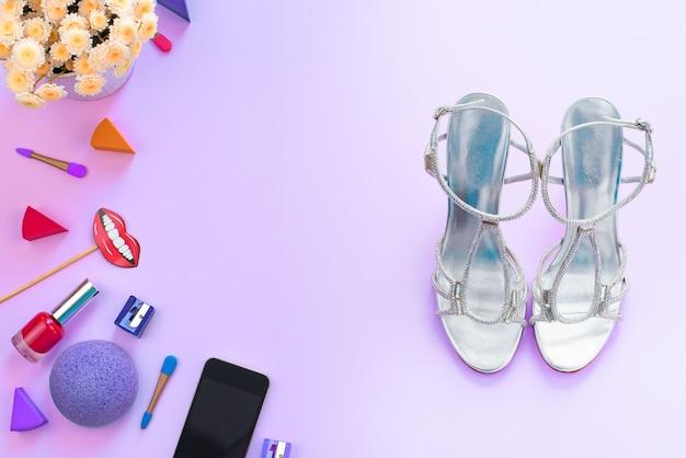 Accesorios cosméticos zapatos gadget flores móviles fondo púrpura