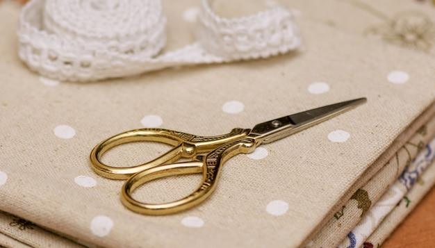 Accesorios de costura - tejidos de costura y tijeras con escamas blancas.