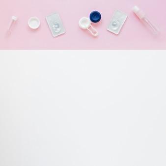 Accesorios para el cuidado de los ojos sobre fondo rosa y blanco