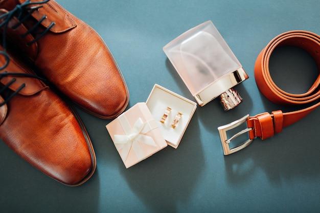 Accesorios para el día de la boda del novio. zapatos de cuero marrón, cinturón, perfume, anillos dorados.