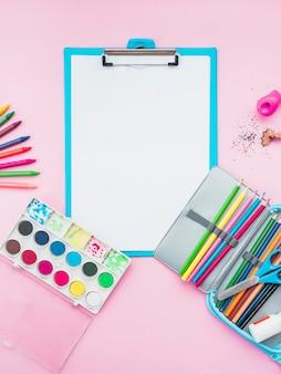 Accesorios de dibujo coloridos y portapapeles sobre el fondo rosa