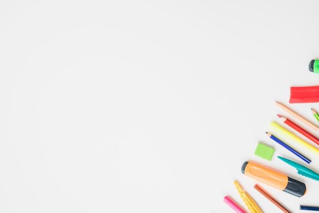 Accesorios escolares de colores en la esquina del fondo blanco.