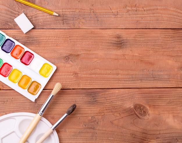 Accesorios escolares y de pintor en mesa de madera