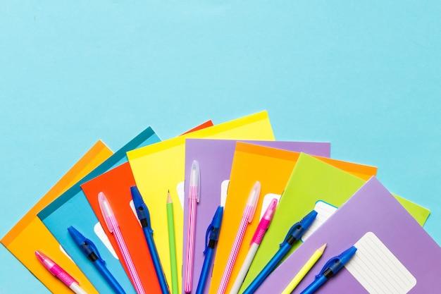 Accesorios para la escuela, cuadernos, bolígrafos, lápices para el lugar de trabajo de un escolar sobre un fondo azul.