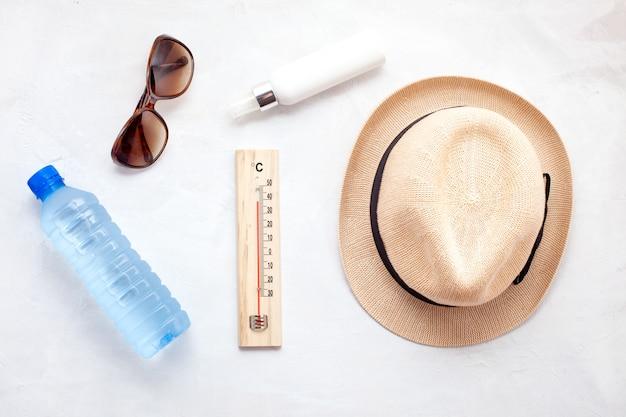 Accesorios esenciales para el calor del verano: gafas de sol, gorro, protector solar y botella de agua. vista plana, vista superior