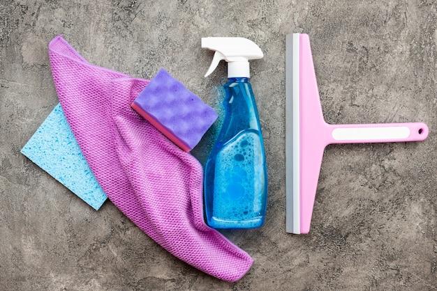 Accesorios para el hogar: spray de lavado, esponjoso, trapo y cepillos de lavado sobre un piso de yeso decorativo gris.