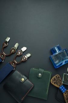 Accesorios para hombres. cartera de hombre, mariposa de hombre, tirantes y perfume sobre fondo oscuro.