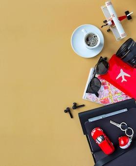 Accesorios para hombres, dispositivos, café, avión, modelo de automóvil, llaves, mapa, lente de cámara sobre fondo camel. concepto de cancelación de viajes y vacaciones, vista superior, espacio plano y copia