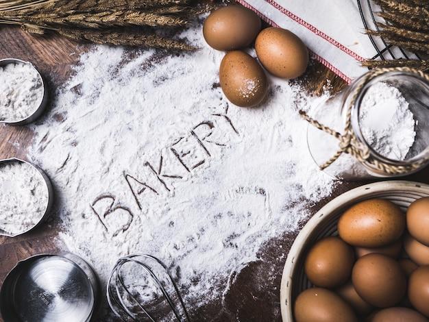 Accesorios para hornear pastelería panadería con texto de panadería escrito en harina.