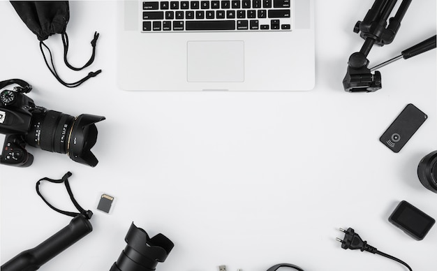 Accesorios para laptop y cámara sobre fondo blanco con espacio de copia