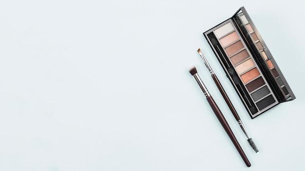 Accesorios de maquillaje en paleta natural sobre fondo claro.