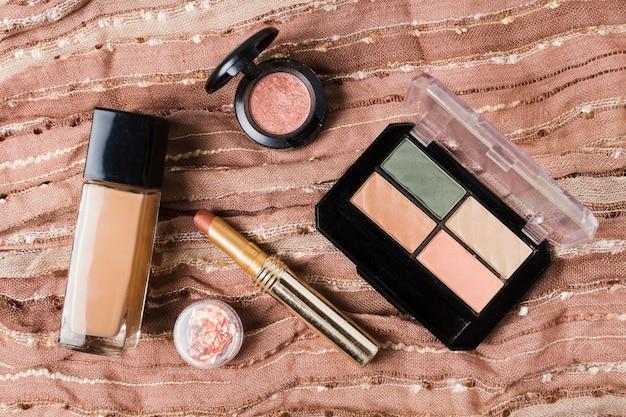 Accesorios para maquillaje sobre tela marrón.