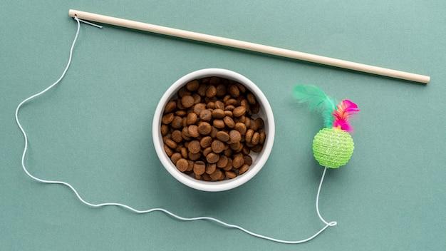 Accesorios para mascotas bodegón con juguete y tazón de comida.