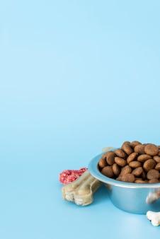 Accesorios para mascotas bodegón con plato de comida y huesos para masticar