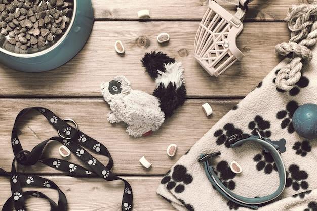 Accesorios para mascotas: collar, correa, bozal, plato de comida, juguetes, alfombra sobre un fondo de madera en estilo vintage. endecha plana