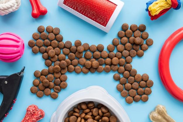 Accesorios para mascotas concepto de naturaleza muerta con comida seca en forma de hueso