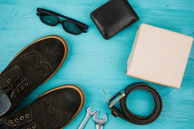 Accesorios masculinos cerca de caja y zapatos.