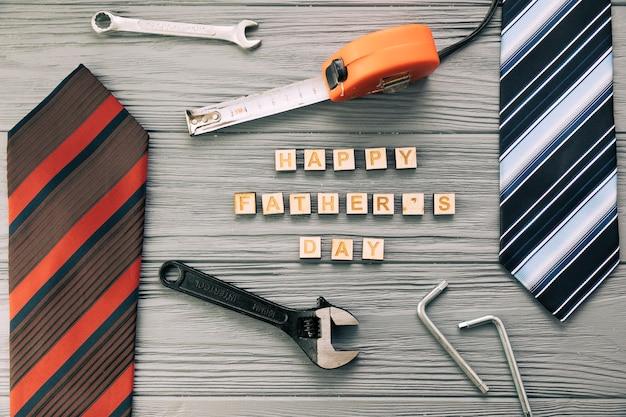 Accesorios masculinos cerca de instrumentos y felices palabras del día del padre con corbatas.