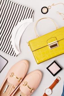 Accesorios de moda femenina, zapatos, camisa, maquillaje y bolso.