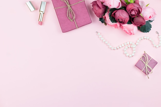 Accesorios de moda mujer, flores, cosméticos y joyas sobre fondo rosa, copyspace.