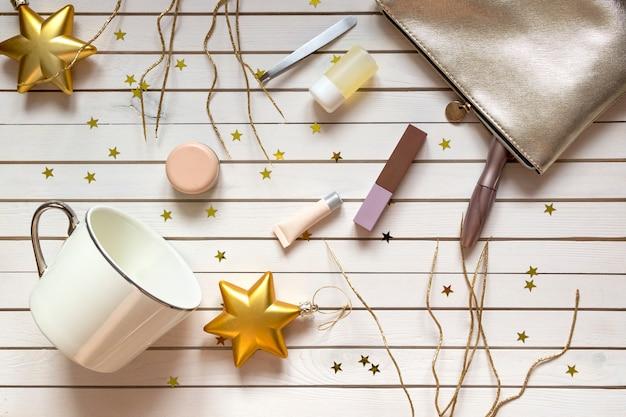 Accesorios de mujer en bolsa de cosméticos, rímel, cremas, lociones, lápiz labial y copa en navidad de madera con estrellas doradas.