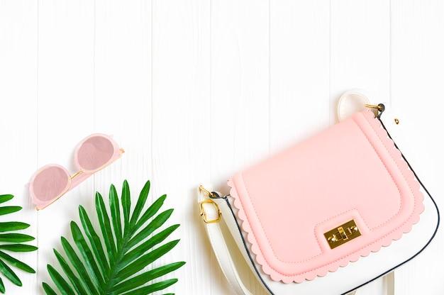 Accesorios para mujer: bolso blanco, rosa, gafas de moda de color rosa con gafas de espejo, hojas de palma sobre fondo de madera blanca