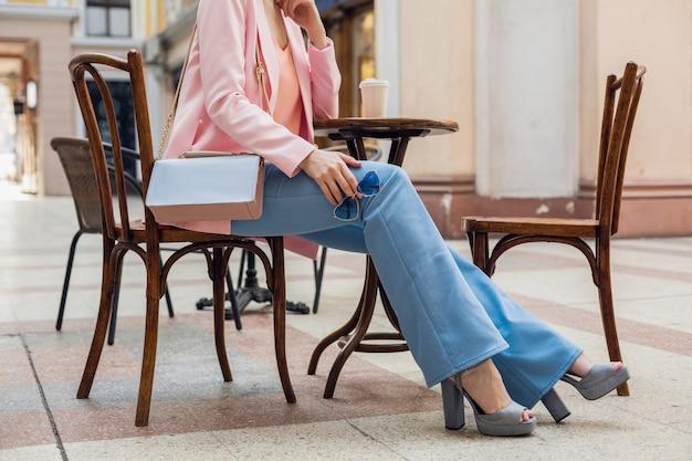 Accesorios de mujer elegante sentada en la cafetería, pinzas de pantalones de estilo vintage, piernas en jeans, zapatos de tacón alto, gafas de sol, bolso, colores rosa y azul, tendencia de moda primavera verano, estilo elegante