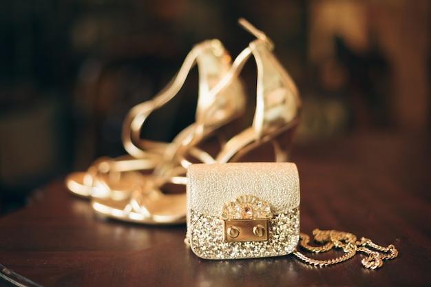 Accesorios de mujer de moda de lujo, zapatos de tacón dorado, monedero de noche, estilo elegante, estilo vintage, calzado sandalias
