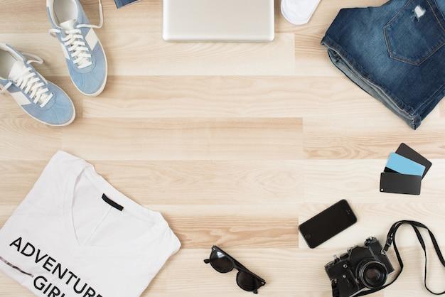 Accesorios de mujer, ropa casual de verano sobre un fondo de madera. artículos de vacaciones y viajes. lat plana, vista superior. agrega tu texto arriba.
