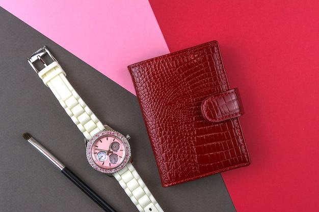 Accesorios de mujer, tarjetero rojo, reloj de pulsera, pincel de maquillaje.
