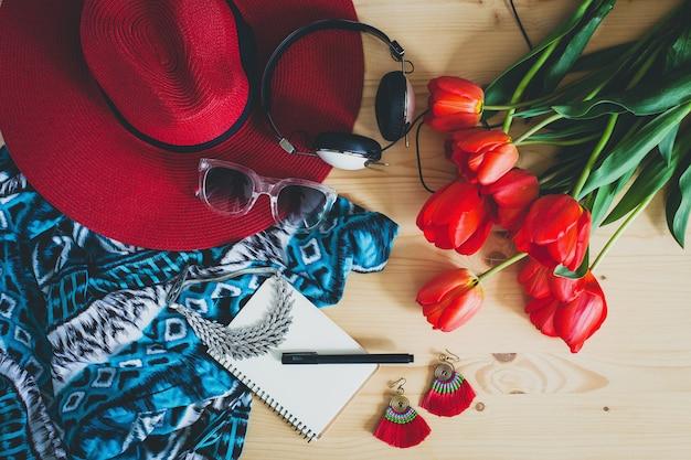 Accesorios de mujer y tulipanes rojos en mesa