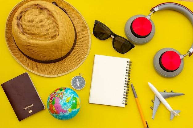 Accesorios y objetos de viaje de verano en espacio de copia de fondo amarillo, para viaje de vacaciones en la playa con cuaderno de cámara de avión, para póster de viaje y anuncio publicitario