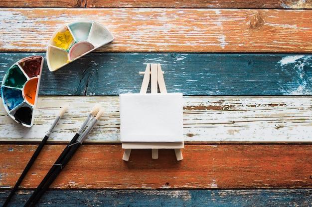Accesorios de pintura con caballete miniatura blanco negro.