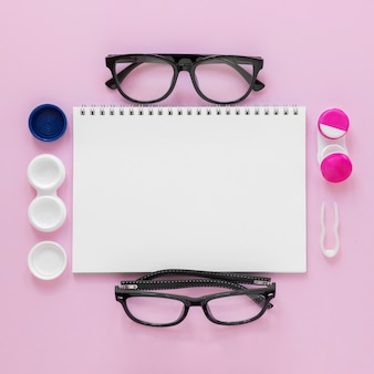 Accesorios planos para el cuidado de los ojos sobre fondo rosa con maqueta de cuaderno